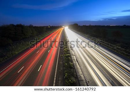 car motorway trails at dusk - stock photo