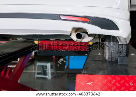 Car muffler in process of being modified in garage - stock photo