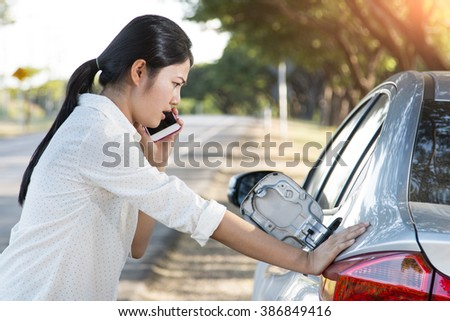 Car oil down and Young woman trying to calling for help on phone. - stock photo