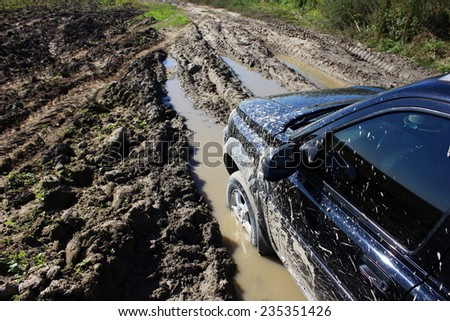 car on a muddy road - stock photo