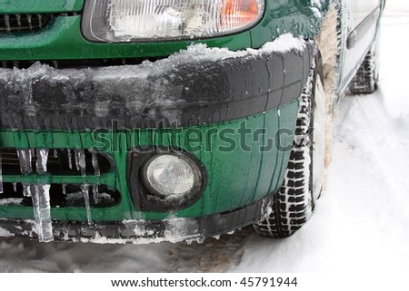 car on a snowy street with icicles - stock photo