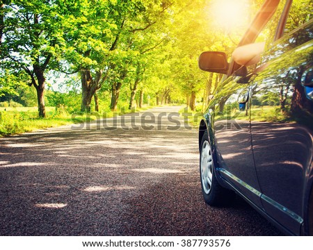 Car on asphalt road in summer - stock photo