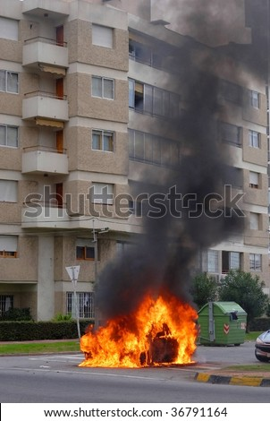 Car on fire and black smoke rising up. Advanced stage of a fire - stock photo