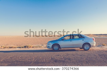 Car on road in prairie at sunset - stock photo