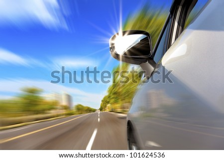 car on the road with motion blur and sunlight in the mirror - stock photo