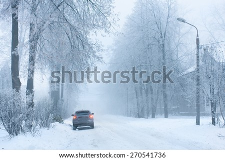 car on the snowy street - stock photo