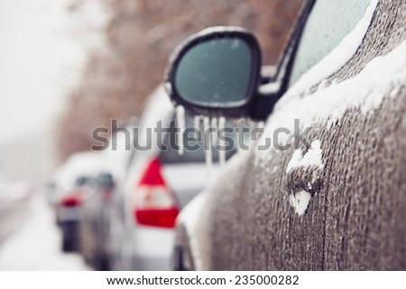 Car on the street covered by icy rain  - stock photo