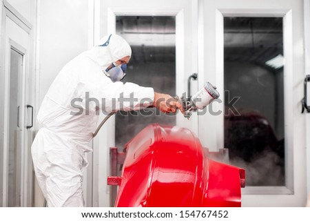 car painter working on a red car in a special painting booth