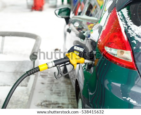 Car refueling on a petrol station in winter closeup