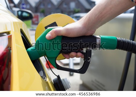 Car refueling on petrol station. Man pumping gasoline fuel in car at gas station - stock photo