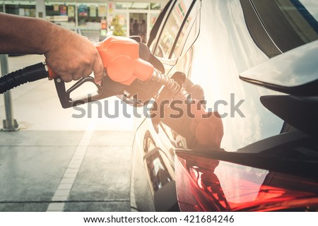 Car refueling on petrol station. To fill the machine with fuel. Car refueling with gasoline at gas station. Fuel pump at station. Man pumping gasoline fuel in car at gas station. - stock photo