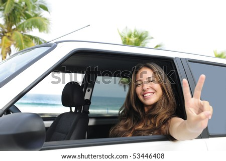 car rental: happy woman in her car near the beach showing victory sign