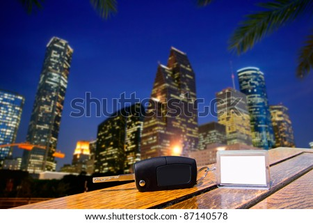 Car rental keys on wood table with blank paper in Houston night downtown [Photo Illustration] - stock photo