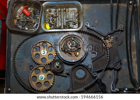 Car repair with belt and gears in grunge iron table - stock photo