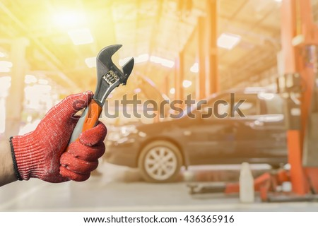 Car repairing,Hand of car technician auto mechanic with a wrench working in garage. Repair service ,car repair station.vintage tone