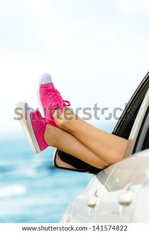 Car road trip vacation concept. Woman legs out the windows on sea background. Female legs out of window for freedom, travel and relax concept. Copy space - stock photo