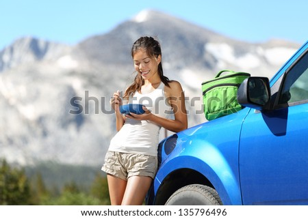 Car road trip woman driver eating lunch break outdoors in mountain landscape in Yosemite National Park, California, USA. Woman on summer holidays roadtrip vacation enjoying nature. - stock photo