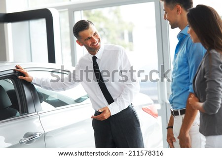 Car Sales Consultant Showing a New Car to a Potential Buyer in Showroom - stock photo