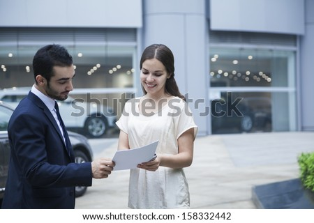 Car salesman and young woman looking over paperwork  - stock photo
