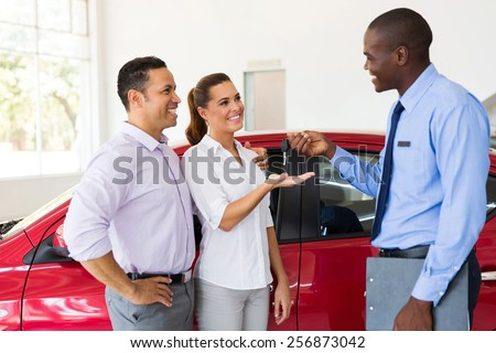 car salesman handing over new car key to couple in car showroom - stock photo