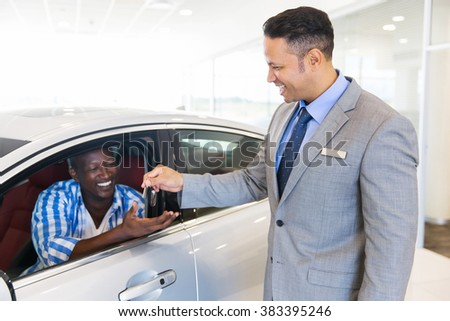 car salesman handing over new car key to customer sitting inside vehicle at showroom - stock photo