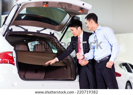 Car salesman in Asian dealership showing trunk of SUV car to customer - stock photo