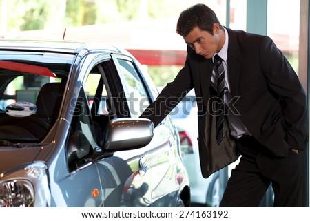 Car salesman looking at new car - stock photo
