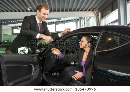 Car salesman sells a car to happy customer in car dealership and hands over the keys. - stock photo