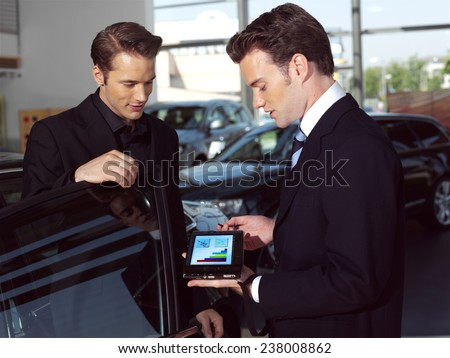 Car salesperson explaining car features to customer - stock photo