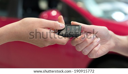 Car saleswoman handing over the keys for a new car to a young woman - stock photo
