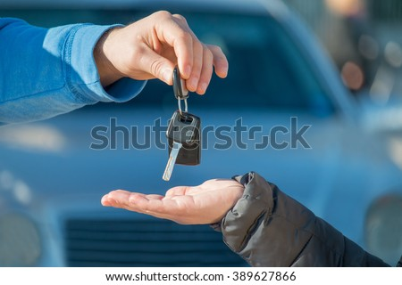 car seller gives the keys to new automobile owner or car rental customer gets the keys  -  rent-a-car or vehicle ownership concept  - stock photo