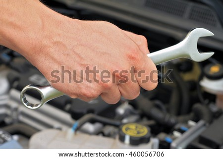 Car service concept, Mechanic Hand Hold Spanner Tool, man checking the condition of car engine.