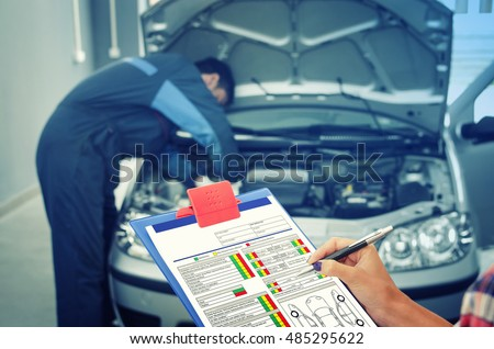 Car service. Holding the check list while car mechanic fixing the car in the background. Maintenance. Car broken down. Car break down. Car broke.