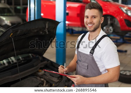 Car service inventory. Smiling mechanic in auto repair shop makes a note on a clipboard - stock photo