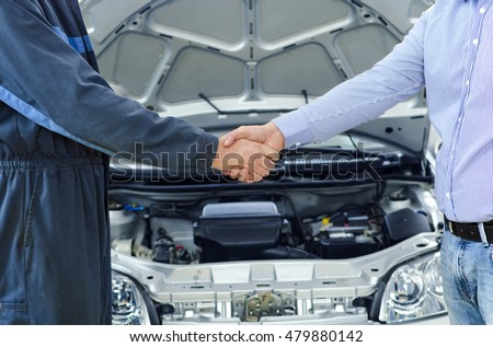 car service mechanic and customer shaking hands excellent cooperation between car mechanic and customer