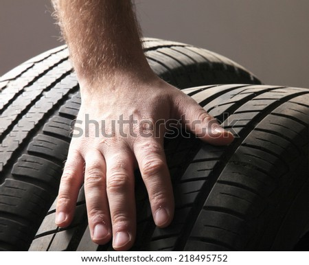 Car service. Wheels and mans hand - stock photo