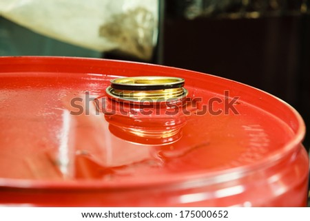 Car servicing  oil change. Red oil barrel canister in mechanic garage auto service or shop. Industry detail. - stock photo