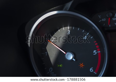 Car tachometer with a scale and a red arrow. - stock photo