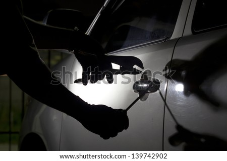 Car thief ,Shot of a male using a tool to break into a car. - stock photo