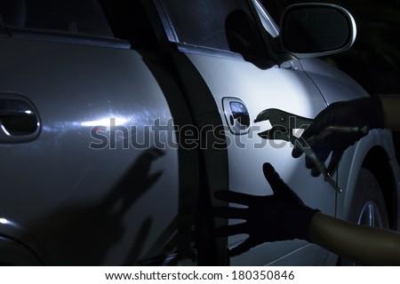 Car thief using a tool to break into a car. - stock photo