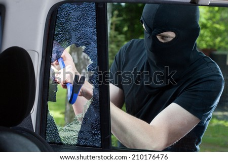 Car thief with crowbar and broken glass - stock photo