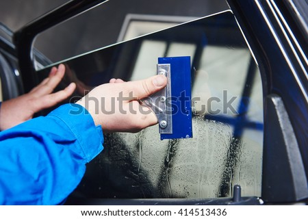 car tinting. Automobile mechanic technician applying foil  - stock photo