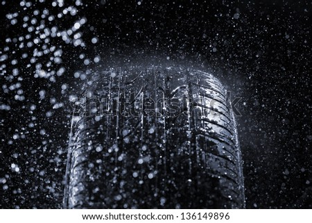 Car tire in rainy conditions. Very short depth-of-field. - stock photo