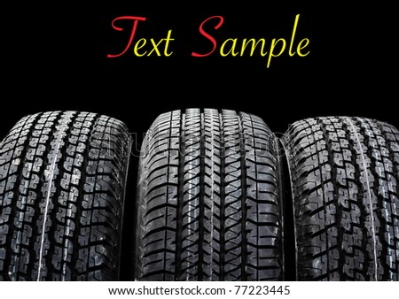 car tire on black background. Useful as background for design-works. - stock photo