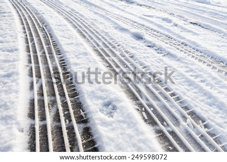 Car tire tracks in snow on road - stock photo
