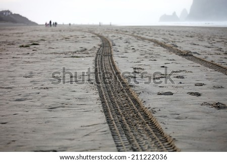 Car tire tracks on Cannon beach in the winter - stock photo