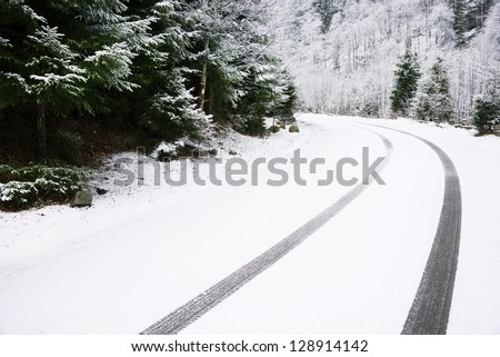 Car tire tracks on the snow, on a mountain road - stock photo