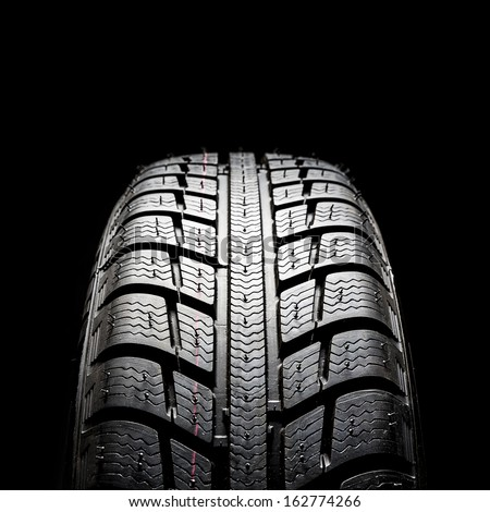 Car tires close-up Winter wheel profile structure on black background - stock photo