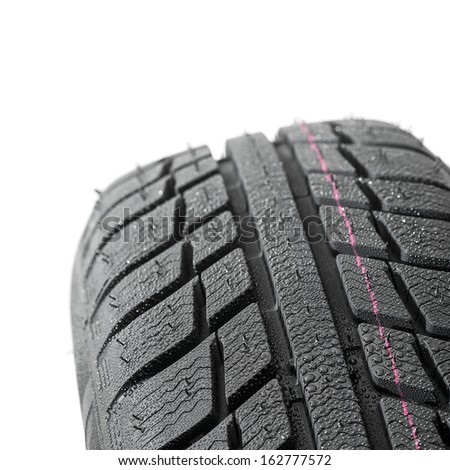 Car tires close-up Winter wheel profile structure with waterdrops on white background - stock photo