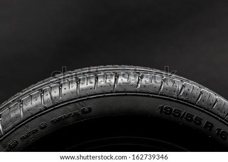 Car tires wheel profile structure on black background - stock photo